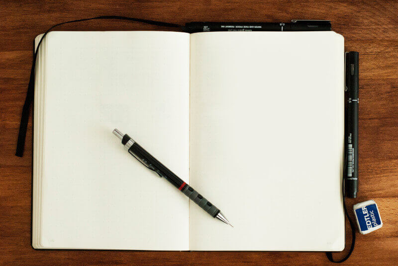 Notatnik z długopisem leży na stole