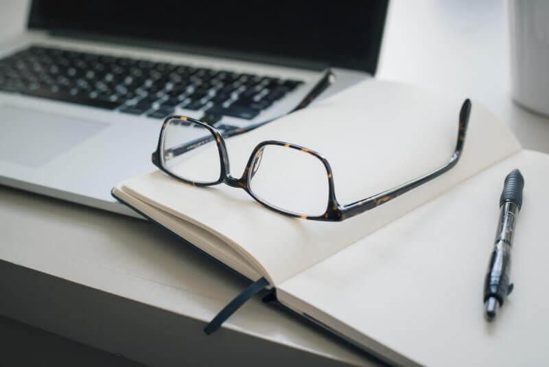 Okulary leżą na notatniku obok laptopa