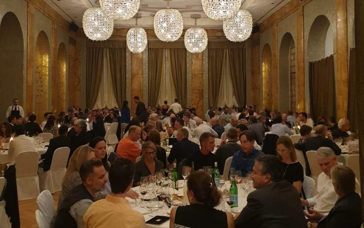 Ludzie rozmawiającyh przy stolikach podczas 2 Symposium Intrauma w Turynie